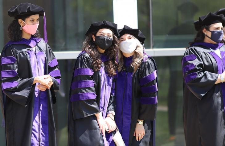 Friends pose at graduation.